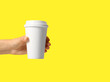 Leinwandbild Motiv Woman holding takeaway paper coffee cup on yellow background, closeup. Space for text