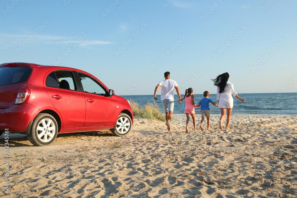 Fototapeta Family running on sandy beach. Summer trip