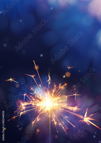 Glittering burning sparkler against fireworks background