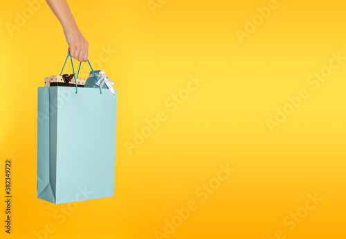 Foto Woman holding paper shopping bag full of gift boxes on yellow background, closeu