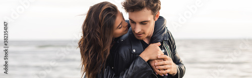 Fotomural Panoramic shot of young woman embracing boyfriend in leather jacket beside sea