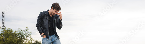 Fototapeta Panoramic shot of man in leather jacket standing outdoors obraz