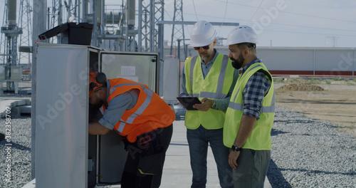 Fotografija Engineer showing power transformer to inspectors