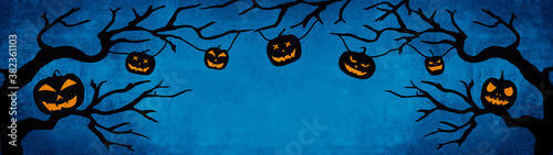 HALLOWEEN background banner wide panoramic panorama template -Silhouette of scary carved luminous cartoon pumpkins hanging on trees isolated on dark blue night texture