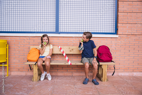 Fotografie, Tablou Children eating an apple at recess sitting on a bench keeping social distance