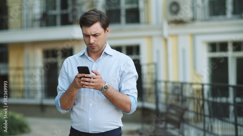 Fototapeta Closeup businessman reading serious news on phone. Man typing on phone at street obraz