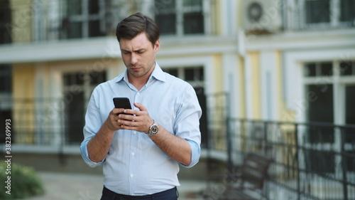 Closeup businessman reading serious news on phone Fotobehang