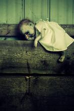 Creepy Doll Sitting On Barn Board