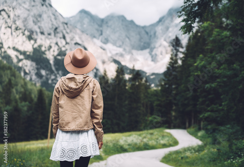 Fototapeta Woman stands on road and looking at mountains. obraz