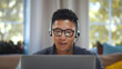 Young asian businessman working on laptop in headset having video conference at home