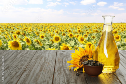 Obraz Sunflower oil and seeds on wooden table near blooming field. Space for text - fototapety do salonu