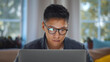 Close up of young asian man in glasses working on laptop at home office