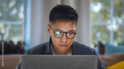 Valokuvatapetti Close up of young asian man in glasses working on laptop at home office