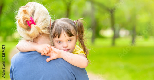 Woman holds in her arms a sad daughter with down syndrome Fototapet
