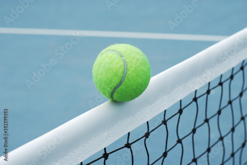 Fotografiet Tennis ball on net  with concrete blue field and white line