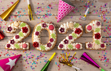 2021 Cake Decorated With Flowers On Wooden Background. New Year Concept