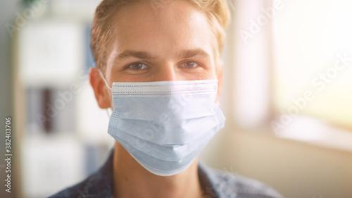 Obraz na plátně Portrait of the Handsome Stylish Young Man Wearing Protective Face Mask Inside