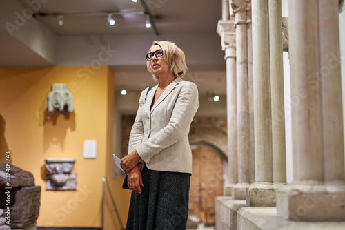 Foto mature woman visitor near columns in the historical museum