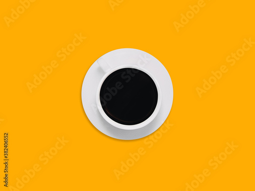 Fototapeta Black coffee Photo in minimal style with copy space White plate with cup of americano is standing on a bright yellow background obraz