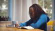 Young african female student sitting at table, using laptop when studying