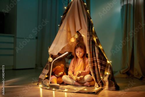 Cuadros en Lienzo A cute girl wearing pyjamas sitting on a floor cross-legged barefoot in a self-m