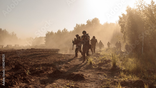 A group of soldiers goes through the field along the forest in the smoke Fototapete