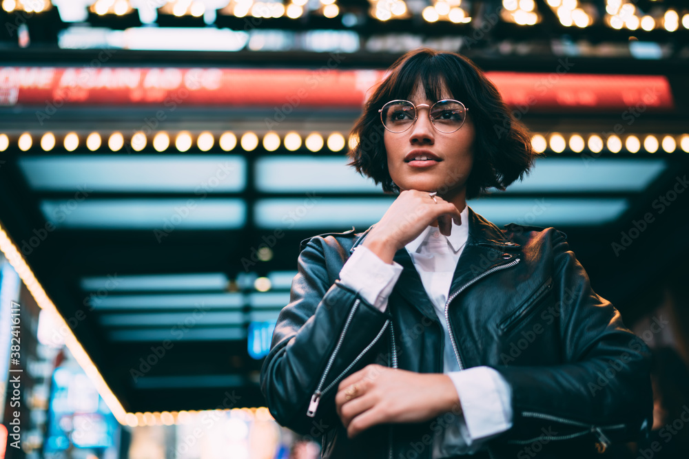 Fototapeta Below view of thoughtful hipster model 20 years old in stylish apparel feeling pondering at illuminated urbanity, trendy dressed Caucasian teenager thinking about metropolitan nightlife lifestyle