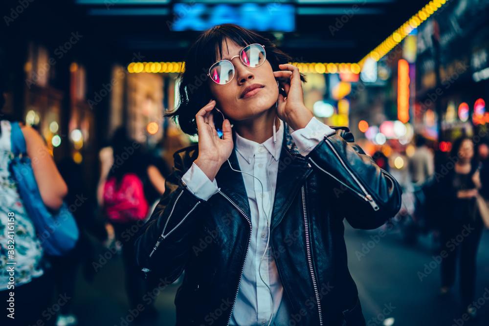 Fototapeta Good looking female millennial in trendy glasses and modern headphones enjoying music podcast, tranquil woman in electronic equipment listening serene audio playlist relaxing at metropolitan street