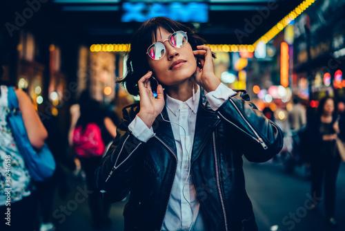 Fototapeta Good looking female millennial in trendy glasses and modern headphones enjoying