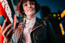 Prosperous Party Girl With Smartphone Technology Enjoying Nightlife In Metropolitan City, Happy Millennial In Optical Eyewear And Modern Headphones Listening Funny Music Set During Evening Walk