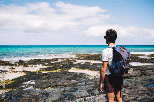 Back view of young backpacker adoring beauty of nature landscape at Menorca coas Canvas Print