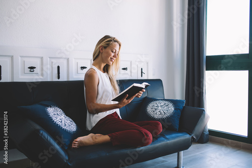 Obraz na plátně Beautiful woman dressed in casual look resting at comfortable couch and reading