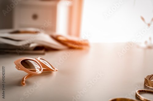 Glasses on the table in the light of the moody sun and the attributes of a woman Wallpaper Mural