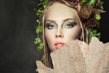 Beautiful Woman With Creative Makeup, Green Leaves And Tree Bark. Halloween Character