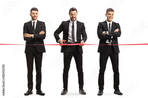 Photo Full length portrait of a three businessmen cutting a red ribbon tape at an even