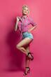 Leinwandbild Motiv Pin-up woman standing on vivid pink background