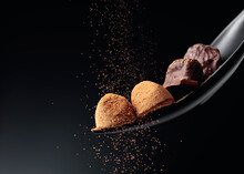 Chocolate Candy Sprinkled With Cocoa Powder On A Dark Background.