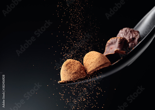 Fotografía Chocolate candy sprinkled with cocoa powder on a dark background.