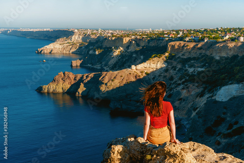 Fototapeta Rear view of traveler woman standing on cliff edge in front of amazing seascape. Freedom, travel and vacation concept. obraz na płótnie