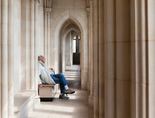 Senior Man Sitting And Have Quiet Moment In Cathedral