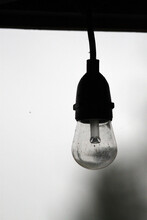 Bare Light Bulb Hanging From A Black Cord