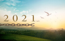 New Year 2021 Concept: Text 2021 With Bird Flying And Broken Chains Over Mountain Sunrise Background