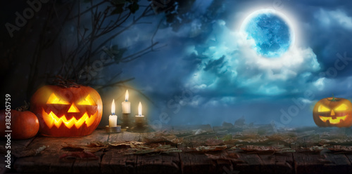 Jack O' Lanterns or Halloween pumpkins and candles glowing at moonlight in the spooky night. Halloween scene   in a mystical forest with moon.