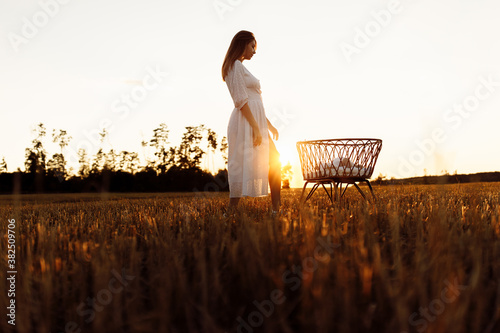Photo Lovely woman near the tiny bed with newborn baby girl at the field, happy mom sp