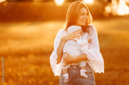 Pretty woman with cute newborn baby girl at the field, loving mother hold beauti Fototapet