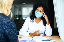 Two Women Having A Financial Business  Consultation With Masks And Social Distancing Due To Coronavirus