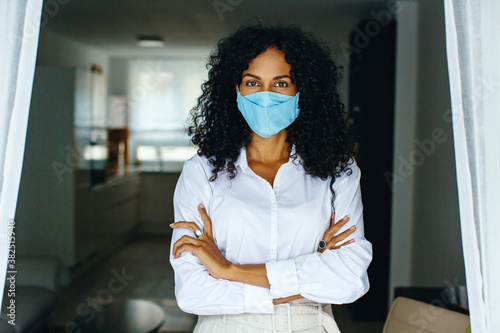 Fotomural Portrait of a woman standing indoors wearing face mask with arms crossed