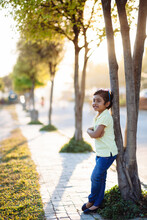 Happy Child Standing Against A Tree On The Pavement,sunny Afternnon
