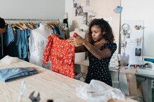 Young Female Business Owner Fashion Entrepreneur Packing Clothing In Box Subscription Delivery Service