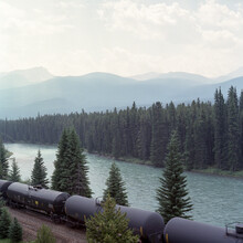 Railroad Tank Cars Pass By A Mountain River.
